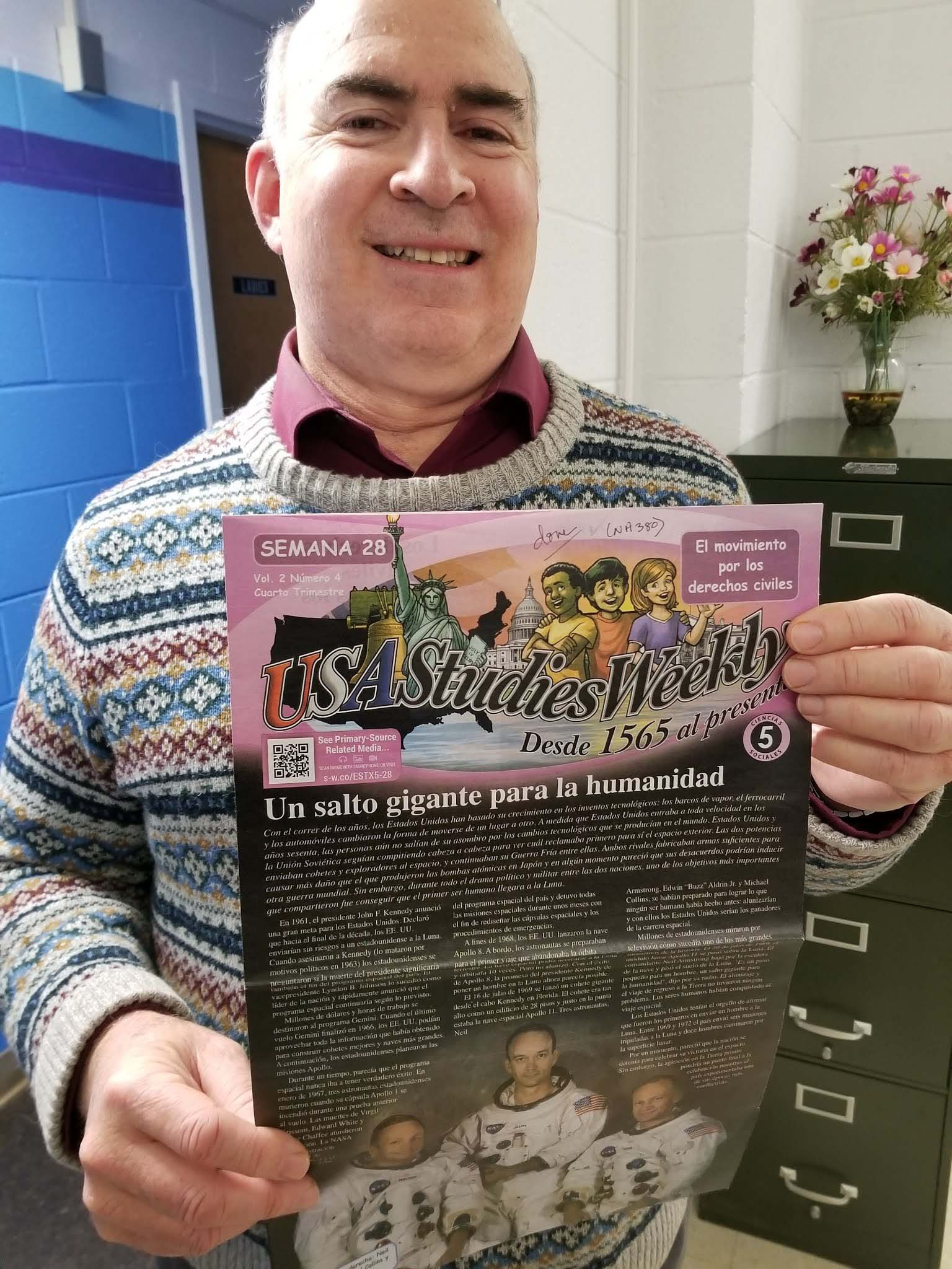 Volunteer David Alper enjoyed reading the Weekly Readers!  In this photo, he is smiling a big smile and holding up a fifth-grade copy about the 1969 moon landing