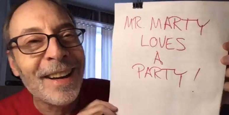 Author Dan Gutman smiles wide and holds up a draft of his next book: Mr. Marty Loves a Party!