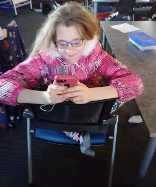 A girl using Learning Ally LINK on her phone while sitting backwards in her chair, with a big smile on her face.