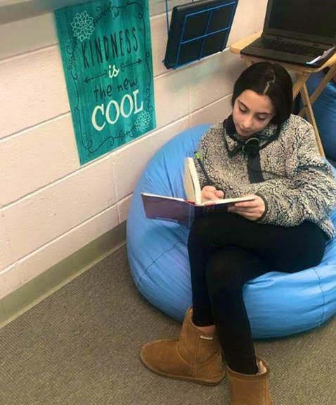 "Image is a screenshot of a middle school girl.  She sitting in a blue bean bag chair, has on a warm fuzzy jacket and warm boots. Her legs are crossed with a book propped on her leg. She has headphones draped around her neck. She has a pencil in her right hand, looking intently at the page and is jotting notes in the book. There is a poster behind her that reads, ""Kindness is the new cool."""