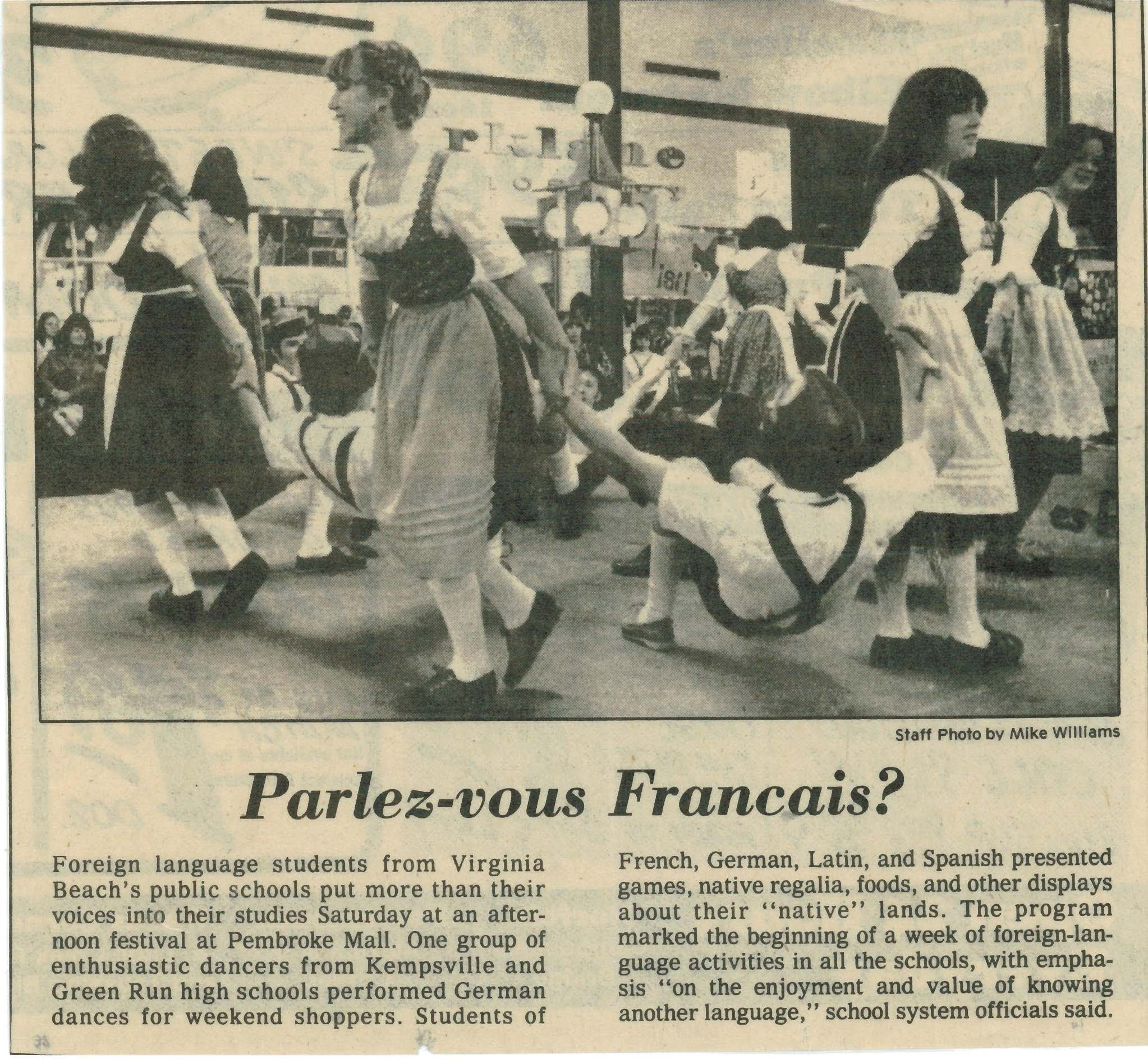 This is a newspaper article showing Stacie Court in high school, dressed in a traditional dirndl with her peers. Stacie is a brunette in the right foreground, holding up her dance partner, Bill, for the highpoint of the Mühlradl, where the guys swing their legs up and down to imitate the workings of a mill).